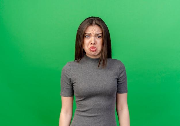 Triste giovane donna graziosa in piedi e guardando la telecamera isolata su sfondo verde con copia spazio
