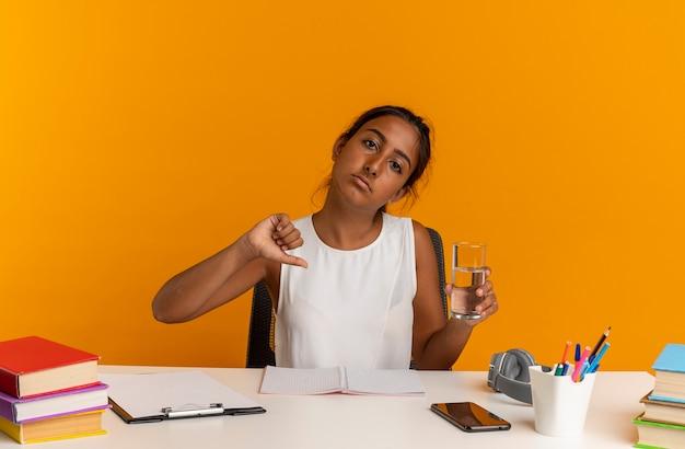 Грустная молодая школьница сидит за столом со школьными инструментами, держа стакан воды большим пальцем вниз, изолированным на оранжевой стене