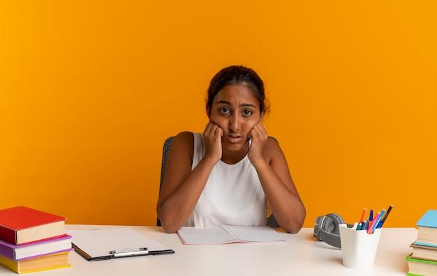 Scolara giovane triste che si siede allo scrittorio con gli strumenti della scuola che mette le mani sulle guance isolate sulla parete arancione