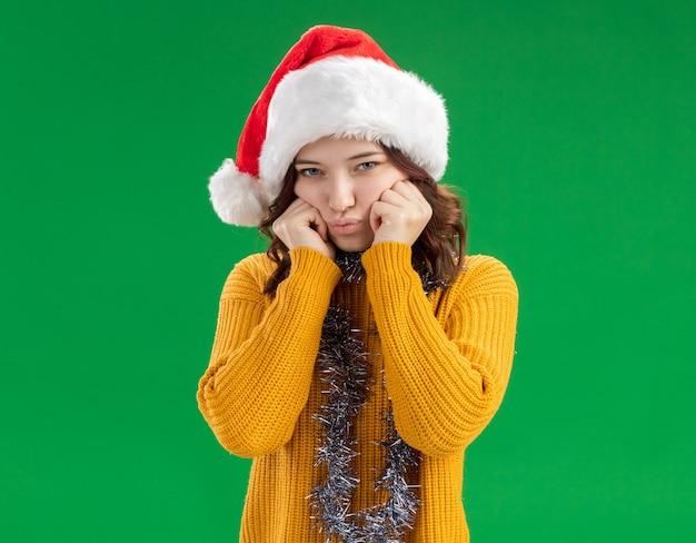 산타 모자와 목 주위에 갈 랜드 슬픈 젊은 슬라브어 소녀 복사 공간이 녹색 배경에 고립 된 얼굴에 손을 넣습니다