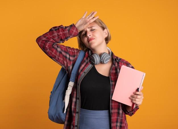 Грустная молодая славянская студентка с наушниками в рюкзаке кладет руку на лоб, держит блокнот и ручку