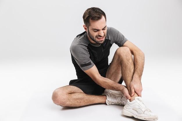 足に痛みを伴う感情で、床に座っている悲しい若いスポーツフィットネス男。