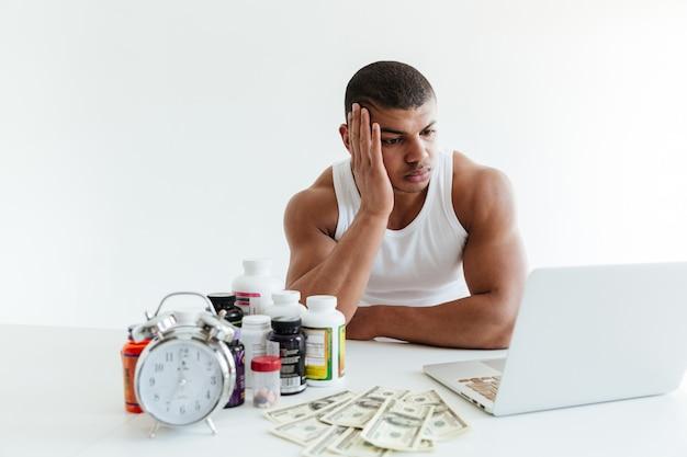 Грустный молодой спортсмен возле денег и спортивного питания с помощью ноутбука