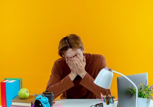 학교 도구와 책상에 앉아 슬픈 젊은 학생 소년 노란색에 손으로 얼굴을 덮여