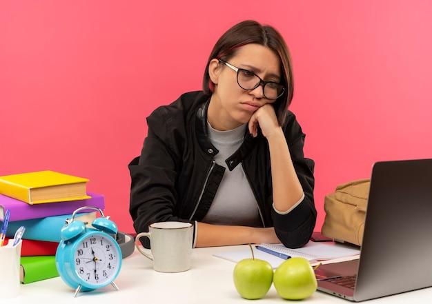 Грустная молодая студентка в очках сидит за столом, делает домашнее задание, положив руку на лицо, глядя на ноутбук, изолированное на розовой стене