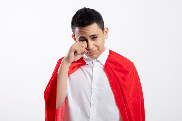 Sad young superhero boy in red cape looking down wiping eye with hand isolated on white background with copy space