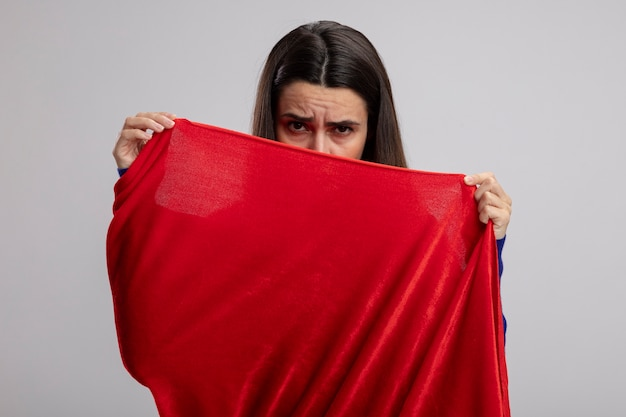Грустная молодая девушка супергероя закрыла лицо плащом, изолированным на белом