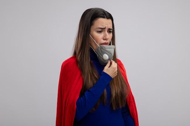 Ragazza triste del supereroe giovane che indossa e ha afferrato la mascherina medica isolata su priorità bassa bianca