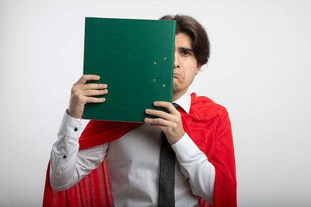 白い背景で隔離クリップボードとネクタイで覆われた顔を身に着けている悲しい若いスーパーヒーローの男