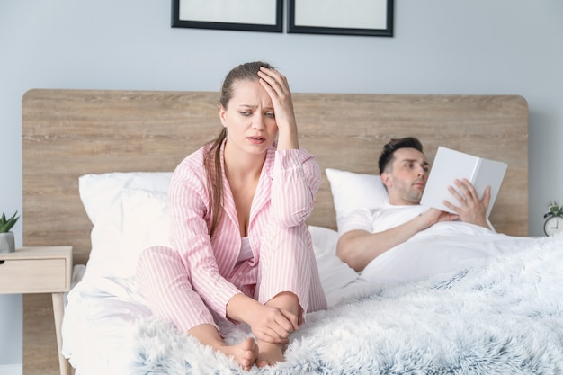 Sad young woman after quarrel with husband sitting on bed