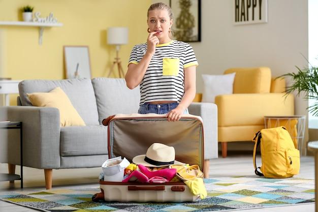 家に物がたくさんある悲しい若い女性とスーツケース。旅行のコンセプト