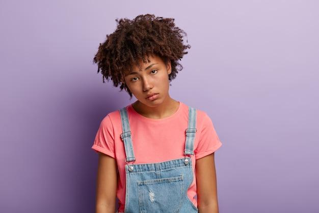 Грустная молодая женщина имеет афро-прическу, апатию в глазах, наклоняет голову, не хочет что-то делать после тяжелой работы, чувствует себя перегруженной, носит повседневную футболку, джинсовый комбинезон, выглядит несчастной прямо в камеру