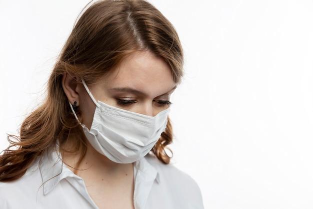 Грустная молодая женщина в медицинской маске склонила голову вниз. карантин во время пандемии коронавируса.