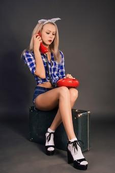 Грустная молодая женщина в рубашке и шортах сидит на старом чемодане и разговаривает по телефону