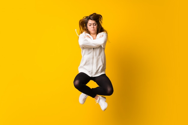 Sad young woman jumping over isolated yellow wall