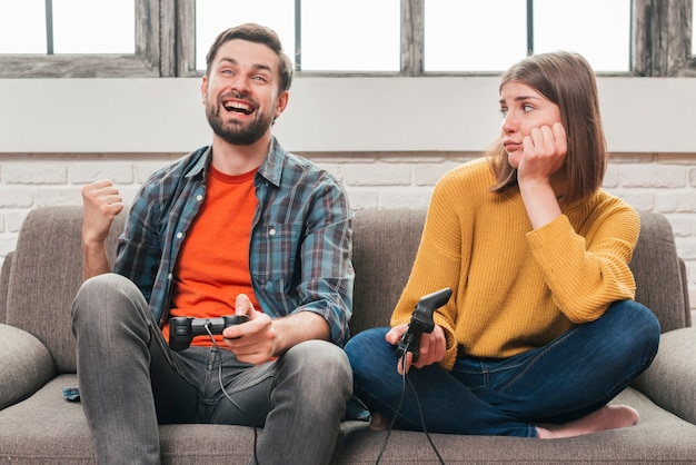 Sad young woman looking at her husband playing the video game with joystick