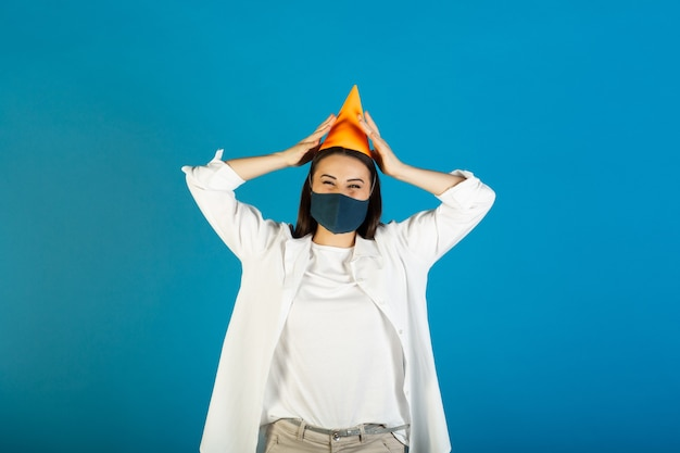 Sad young woman in medical mask in yellow birthday hat on blue