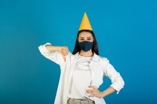 Sad young woman in medical mask in yellow birthday hat showing thumb down on blue