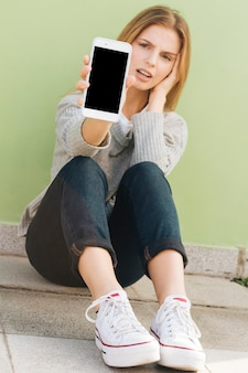 Sad young woman sitting against the green wall showing mobile phone