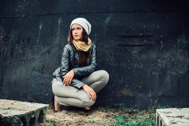黒い壁の近くに座っている悲しい若い女性