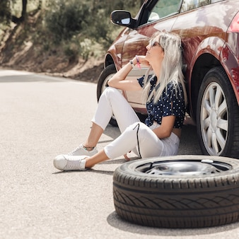 Sad young woman sitting near the broken down car on road
