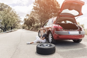 Sad young woman sitting near the broken down car on straight road