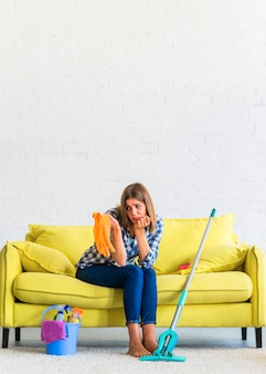 Sad young woman sitting on yellow sofa looking at orange rubber gloves