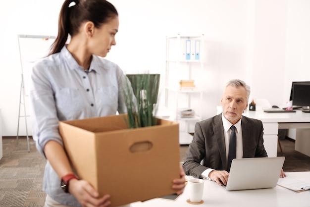 脇を見ながら大きな箱を持って横顔に立っている悲しい若い女性
