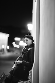 도시 건물 근처에 서 있는 슬픈 젊은 여자
