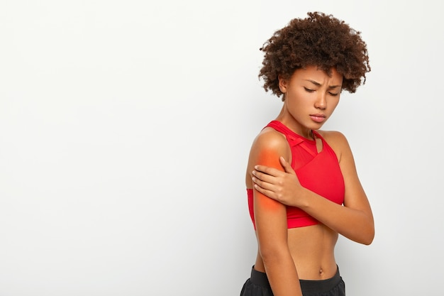 Sad young woman suffers from painful feeling in arm muscle, stands sideways against white background, injured shoulder during workout session