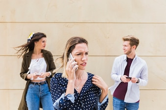 Sad young woman talking on mobile phone standing in front of friends looking at each other