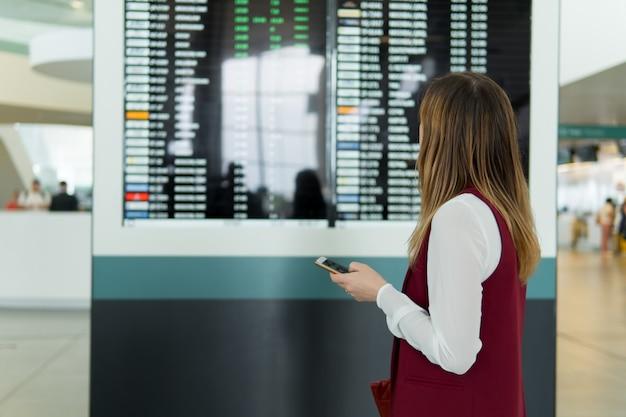 悲しい若い女性は飛行機に遅れ、ぼやけたスコアボードの背景に通知とルックスとスマートフォンで入力して立っています。