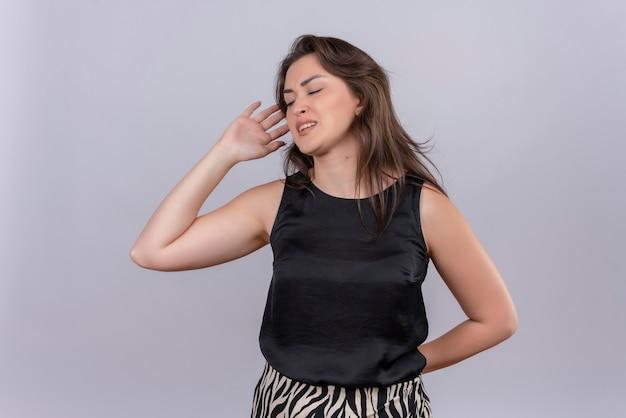 La giovane donna triste che porta la maglietta nera ha messo la sua mano sulla parte posteriore sulla parete bianca