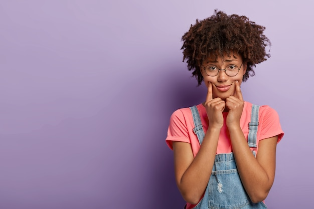 Sad young woman with an afro posing in overalls