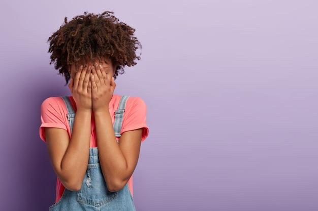 オーバーオールでポーズをとってアフロと悲しい若い女性
