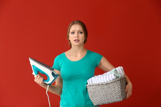 Sad young woman with iron and clean clothes on color