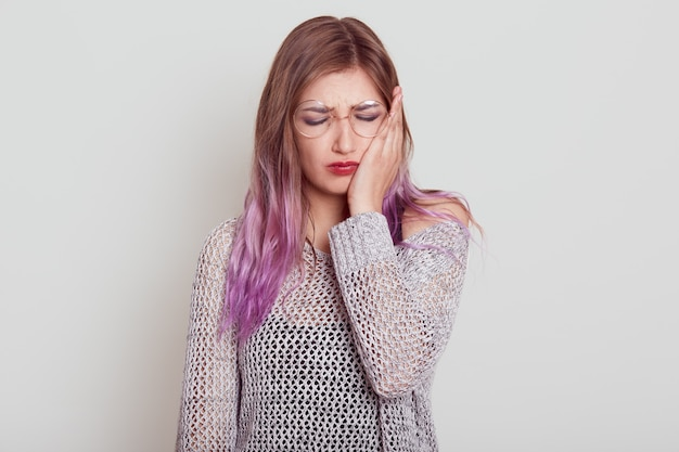 Giovane donna triste con i capelli lilla che soffre di un terribile mal di denti, che si tocca la guancia con il palmo, tiene gli occhi chiusi, il viso accigliato, isolato su sfondo grigio.
