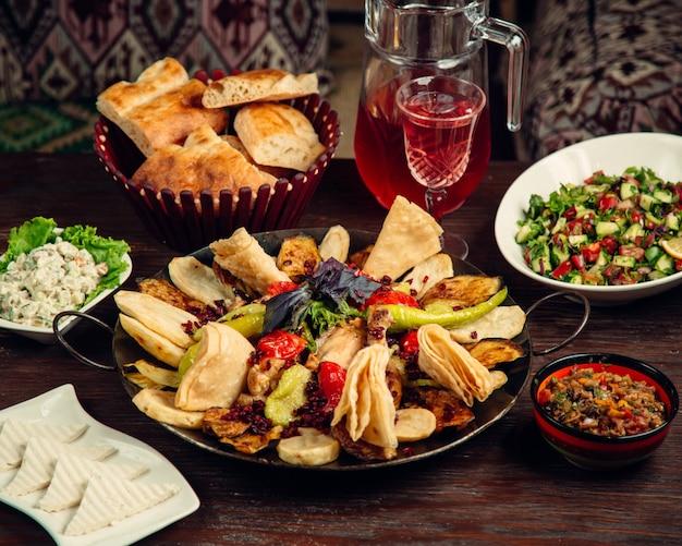 Sadj in iron pot with various salads