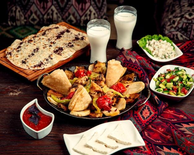 Sadj with shepherd salad and glasses of ayran