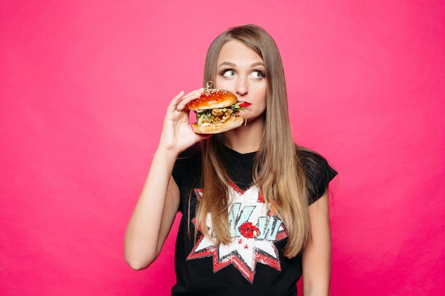 Sadly girl thinking eating tasty humburger or no.