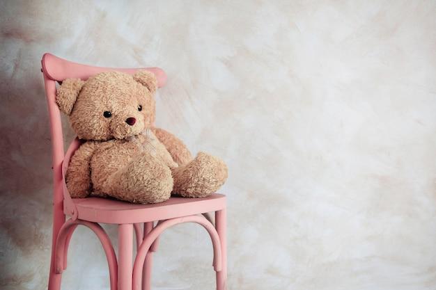 Концепция грусти и одиночества. игрушка одинокого плюшевого медведя, сидящая на стуле в доме
