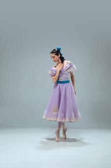 비애. 회색 스튜디오 배경에 고립 된 아름 다운 현대 볼룸 댄서. 왈츠, 탱고, 슬로우 폭스, 퀵 스텝을 춤추는 감각적 인 프로페셔널 아티스트. 유연하고 무중력.