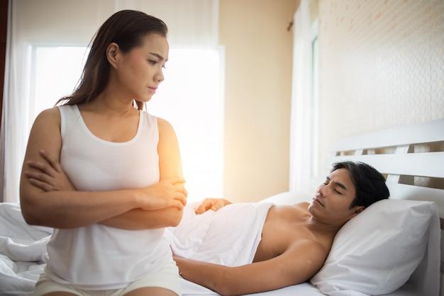 슬픔 여자 친구는 침대에 앉아 그녀의 남자 친구와의 관계 문제를 생각