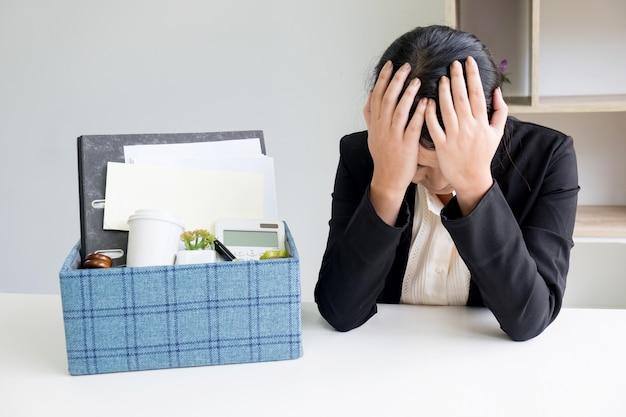 슬픔 예쁜 여성 회사원은 화가 생각하고 미래의 직업을 생각 책상에 앉아 개인 소지품을 포장 해고됩니다.
