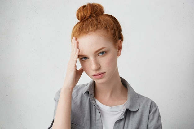 Sadness and sorrow. sad girl wearing her ginger hair in bun holding forehead and looking with upset expression, feeling unhappy