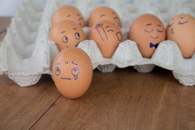 Sadness on wedding eggs face action on egg-shell in brown paper box.
