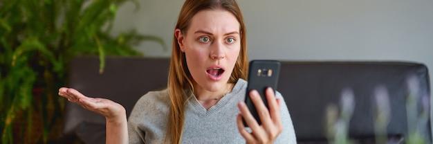 ノートパソコンでソファに座って、自宅で電話で話している悲しみの女性。ノートパソコンと電話を使用して勉強している大学生。
