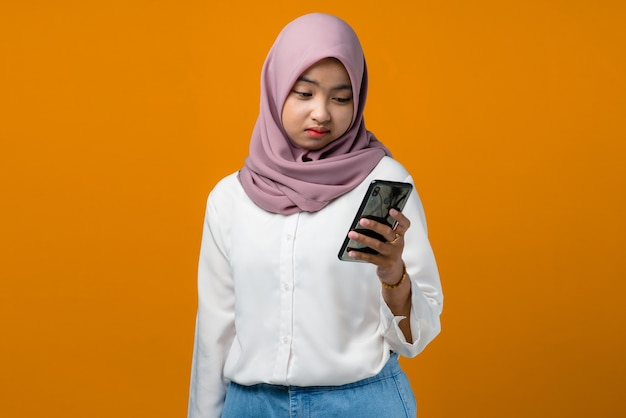 Sadness young asian woman using mobile phone on yellow