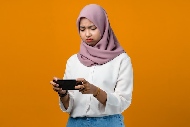 Sadness young asian woman using smartphone on yellow