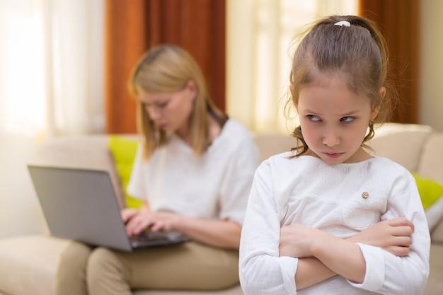 Маленькая девочка печали. портрет скучно дочери с матерью с помощью ноутбука на софе. семейные отношения.